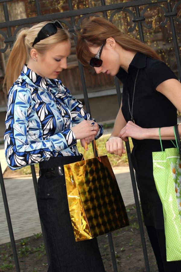 Donne d'acquisto che esaminano le loro vigilanze fotografie stock