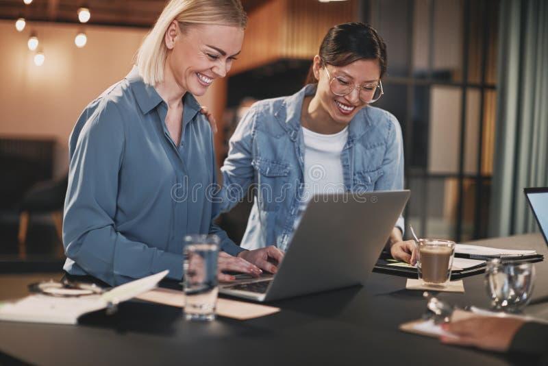 Donne d'affari sorridenti che lavorano su un portatile durante una riunione d'ufficio fotografie stock