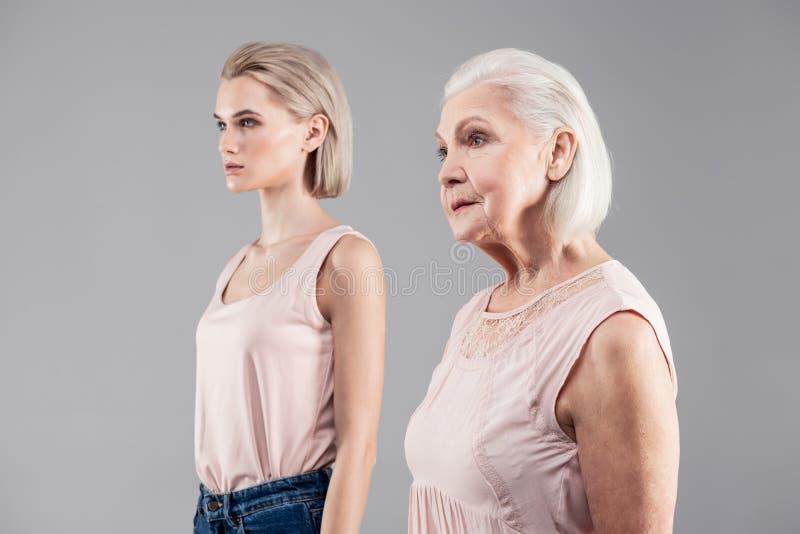 Donne dai capelli corti delle età differenti che si mostrano dal lato immagine stock