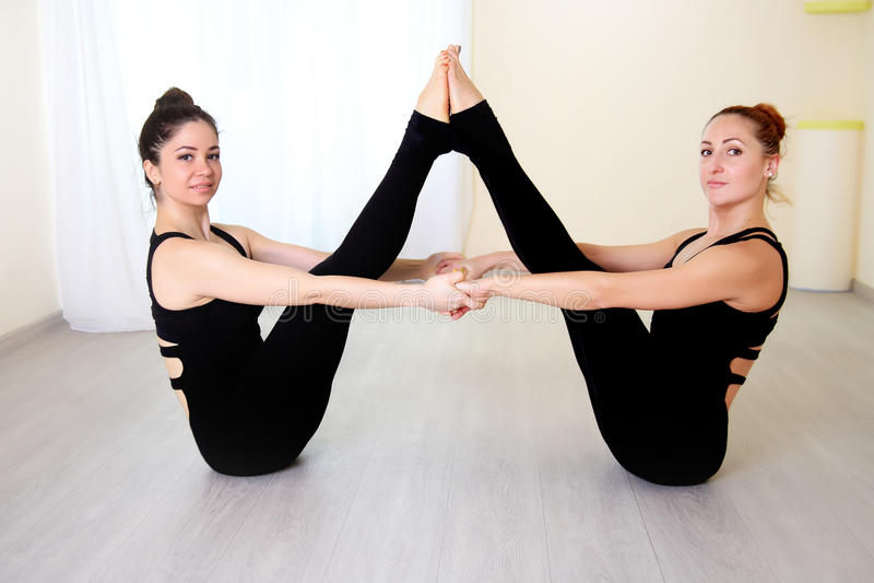 Donne della ginnasta che fanno allungando esercizio nell'interno bianco fotografia stock