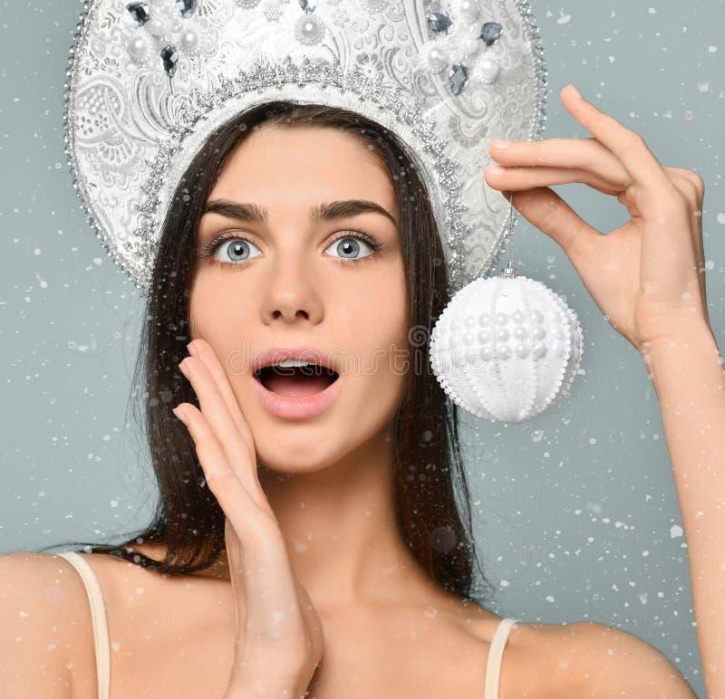 Donne della Santa con i sacchetti Fronte sveglio Pelle sana la ragazza tiene in sua mano una palla dell'albero di Natale fotografia stock