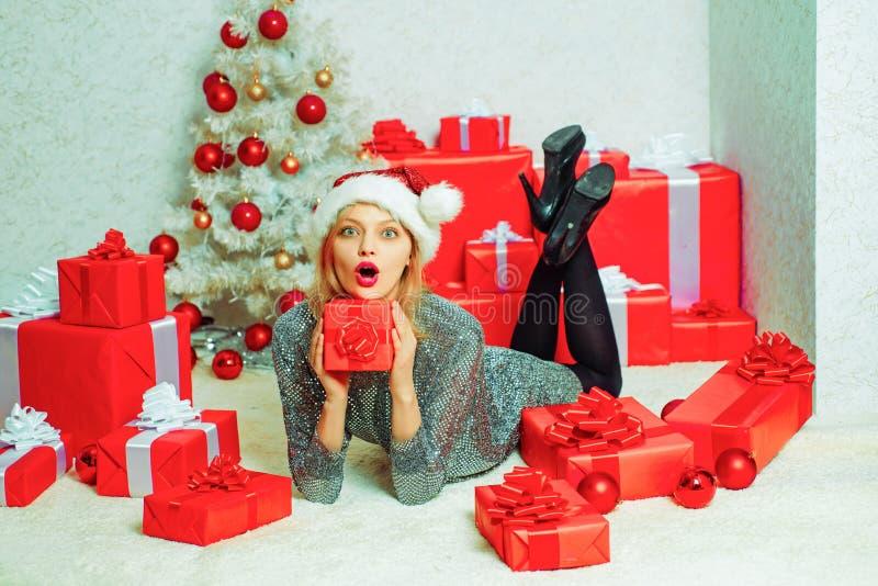 Donne della Santa con i sacchetti Il modello Girl di bellezza in Santa Hat su progettazione domestica decora euphoria Giovane don fotografia stock