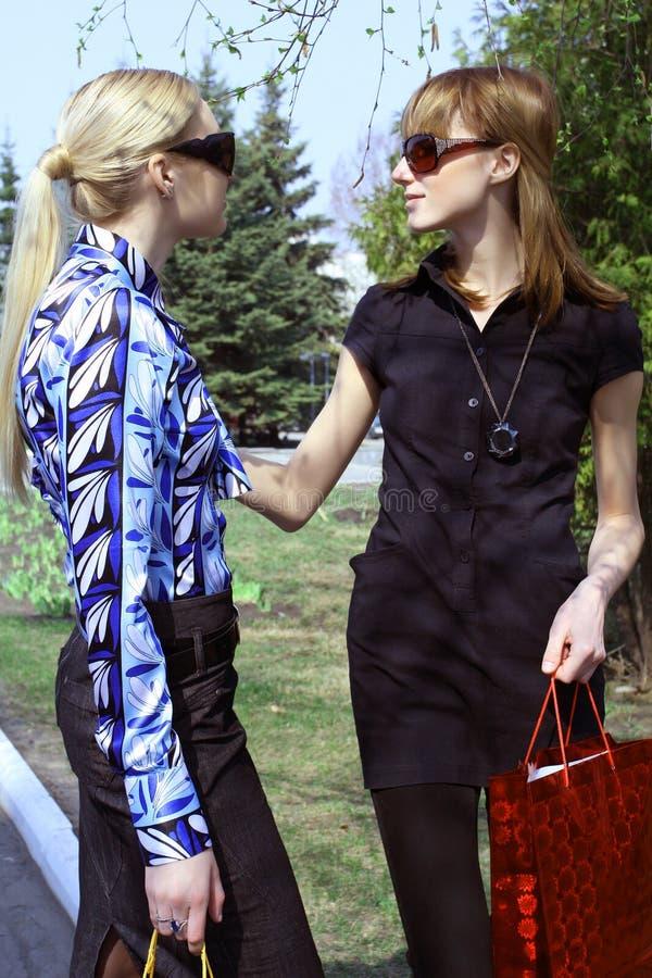 Donne di acquisto che comunicano sulla via fotografie stock