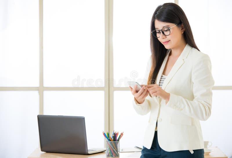 Donne di affari attraenti asiatiche che usando invio di messaggi di testo dello Smart Phone fotografia stock libera da diritti