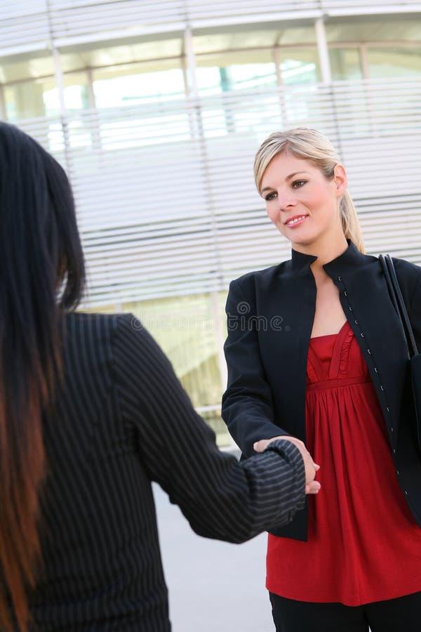 Donne di affari che agitano le mani fotografie stock