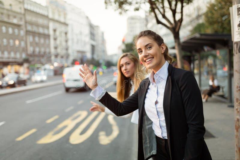 Donne di affari che ondeggiano per il taxi fotografia stock