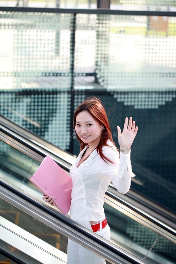 Donne di affari che tengono dispositivo di piegatura sulla scala mobile immagine stock