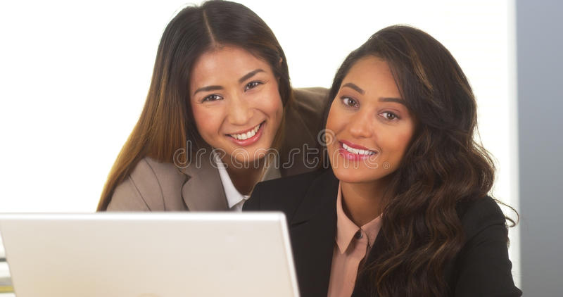 Donne di affari della corsa mista che sorridono alla macchina fotografica immagine stock libera da diritti