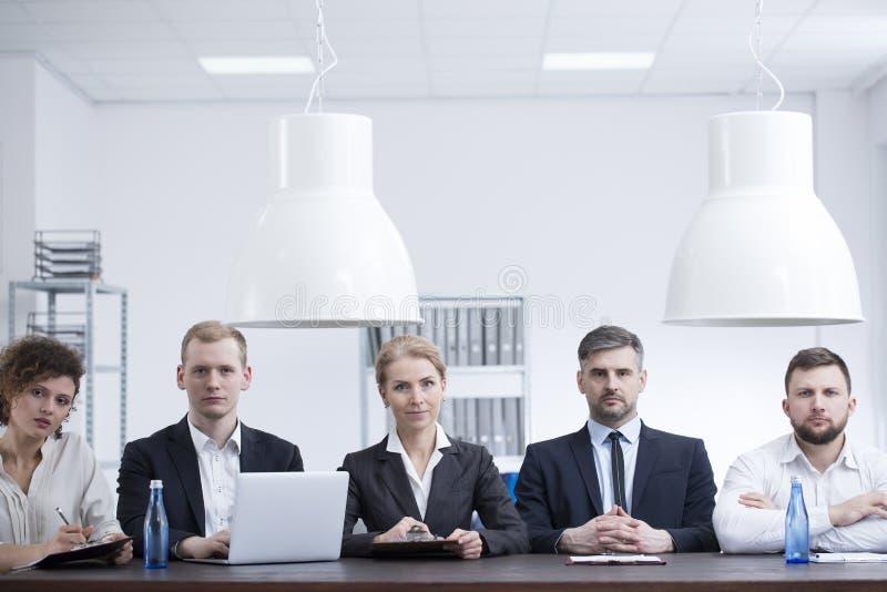 Donne di affari ed uomini d'affari nel corso della riunione fotografie stock
