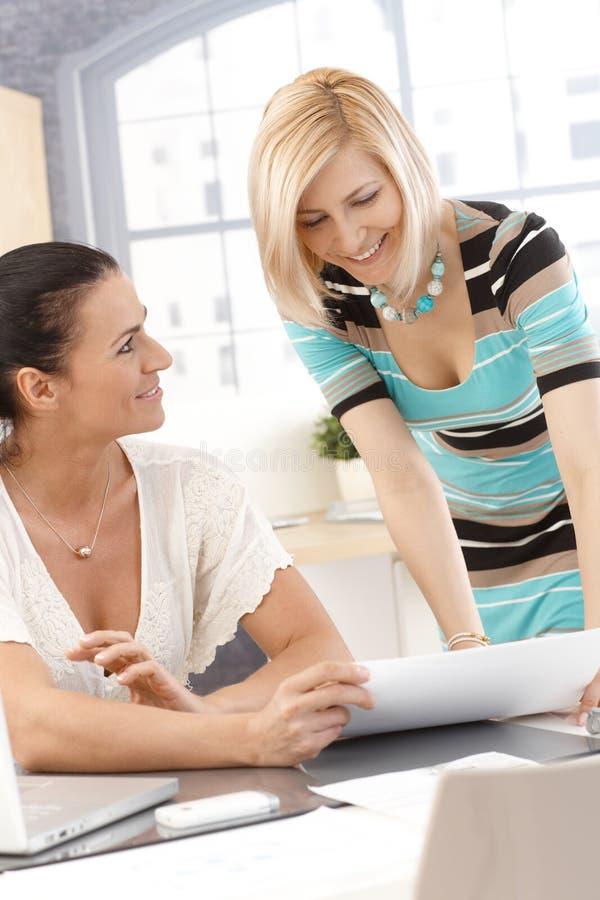 Donne di affari felici che godono del successo all'ufficio fotografia stock
