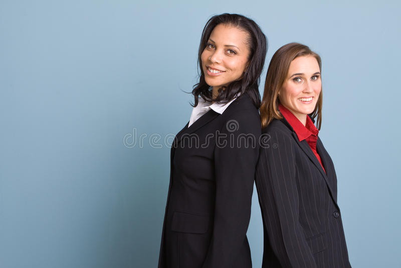 Donne di affari sicure felici che sorridono sul lavoro fotografia stock