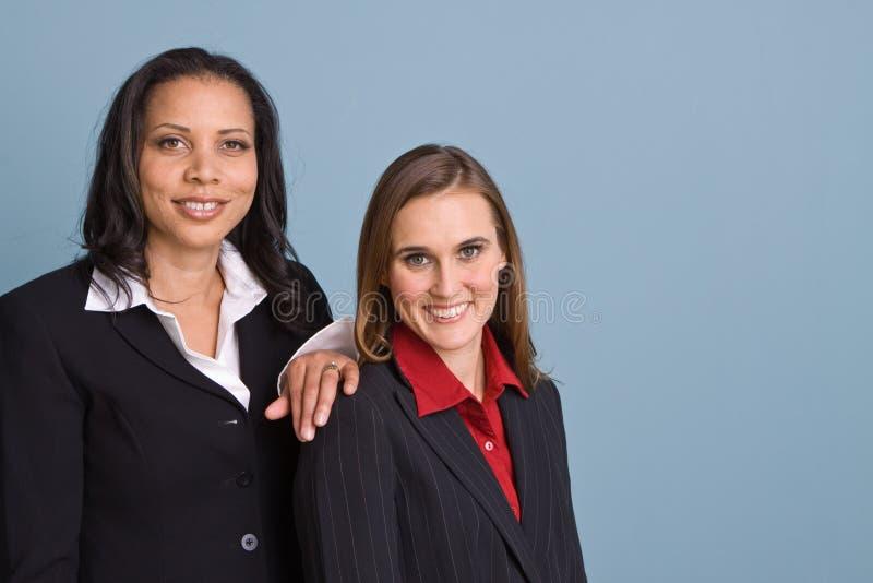 Donne di affari sicure felici che sorridono sul lavoro immagine stock libera da diritti