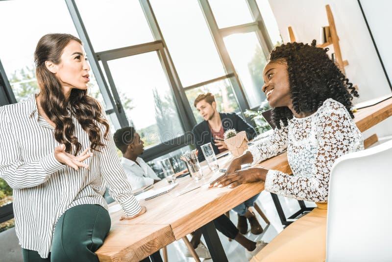 donne di affari sorridenti multietniche che hanno conversazione nel luogo di lavoro immagine stock libera da diritti