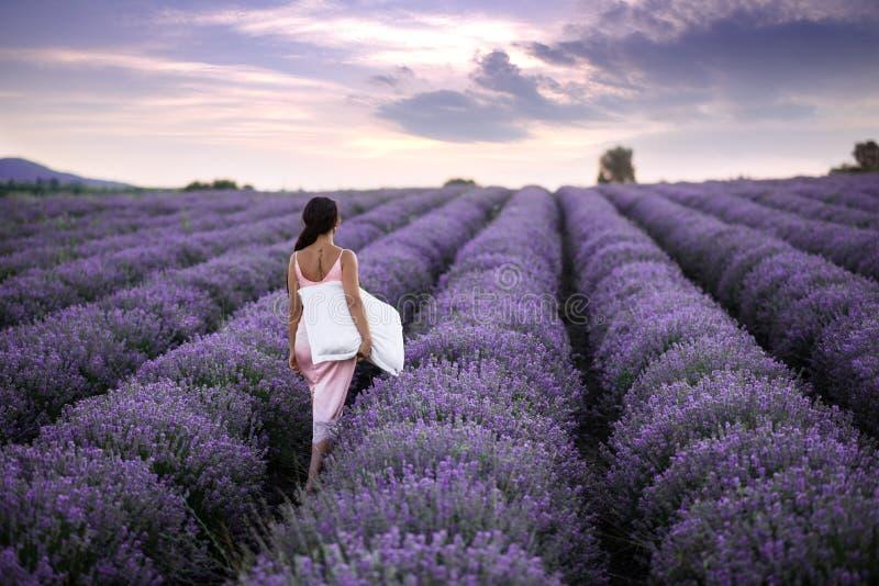 Donne di camminata nel campo di lavanda Donne romantiche nei giacimenti della lavanda La ragazza ammira il tramonto nei giaciment immagini stock libere da diritti