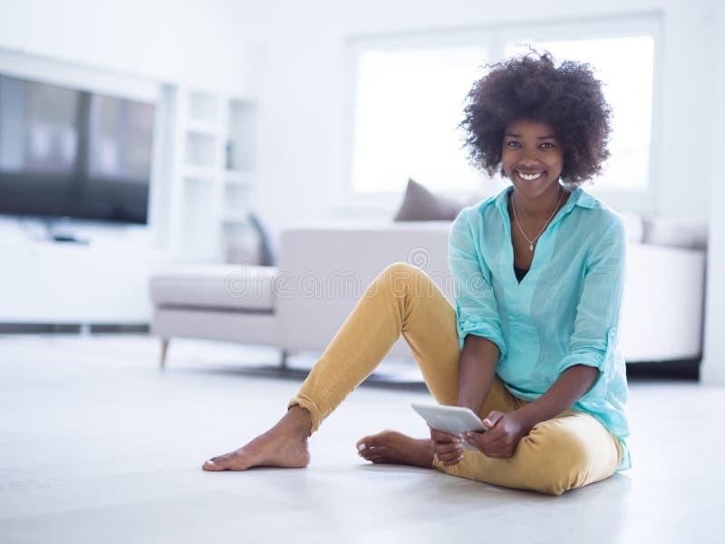 Donne di colore che per mezzo del computer della compressa sul pavimento a casa immagini stock libere da diritti
