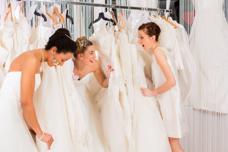 Donne divertendosi durante il vestito nuziale che va d'accordo negozio fotografia stock libera da diritti