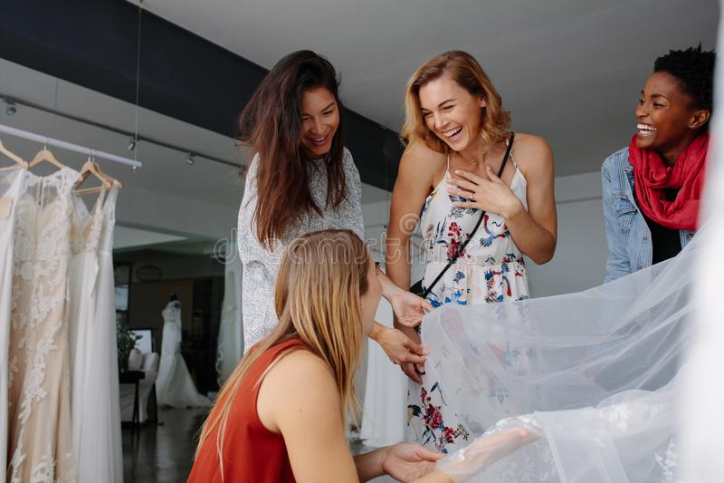 Donne divertendosi durante la selezione dell'abito nuziale in boutique immagini stock