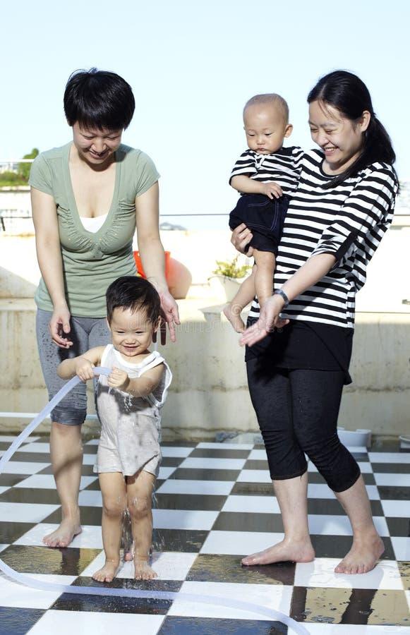 Donne e gioco di bambini asiatici con acqua immagini stock