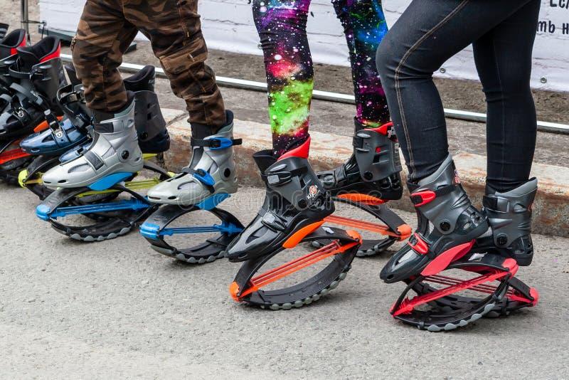 Donne e le gambe dei bambini in ghette e stivali di salto con le molle immagini stock