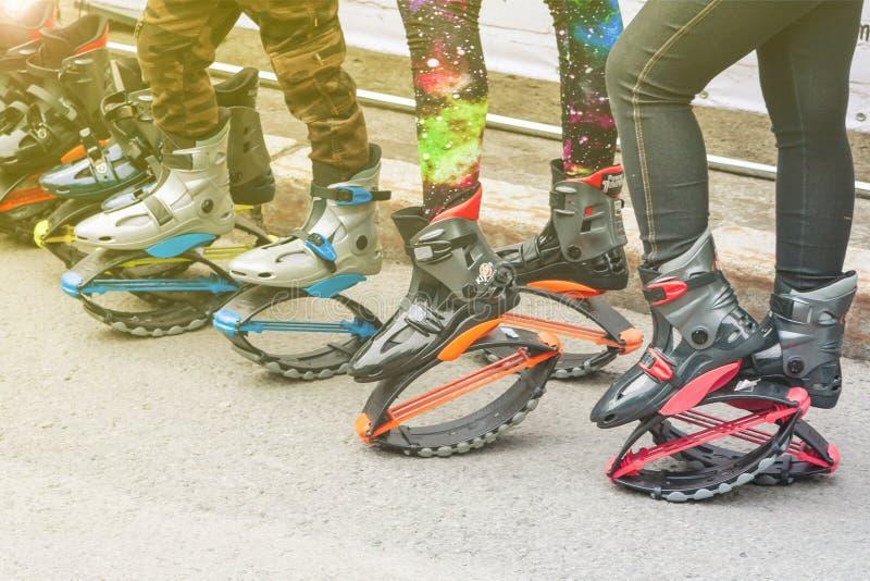 Donne e le gambe dei bambini in ghette e stivali di salto con le molle fotografia stock libera da diritti