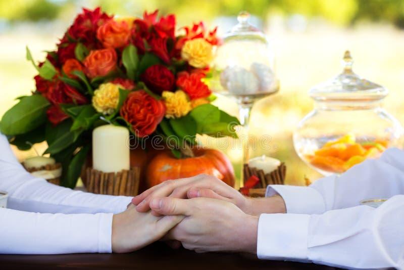 Donne e le mani degli uomini con le fedi nuziali ad una tavola decorata fotografie stock libere da diritti