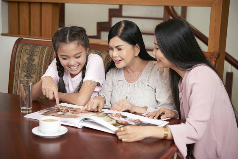 Donne e ragazza felici dei parenti con l'album di foto fotografia stock