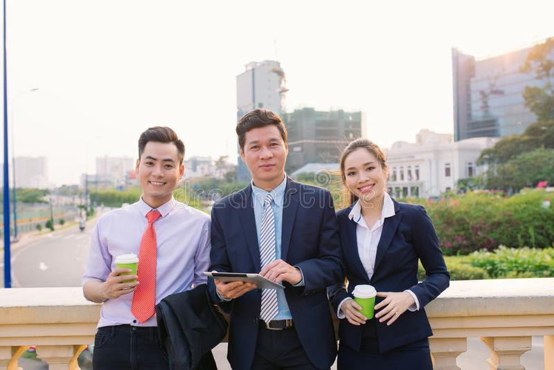 Donne e uomini d'affari asiatici che lavorano fuori dal Tablet PC fotografia stock libera da diritti