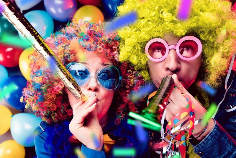 Donne ed uomini che celebrano al partito per la vigilia o il carnevale dei nuovi anni immagini stock