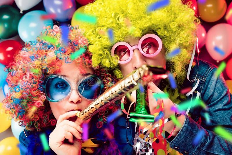 Donne ed uomini che celebrano al partito per la vigilia o il carnevale dei nuovi anni fotografie stock libere da diritti