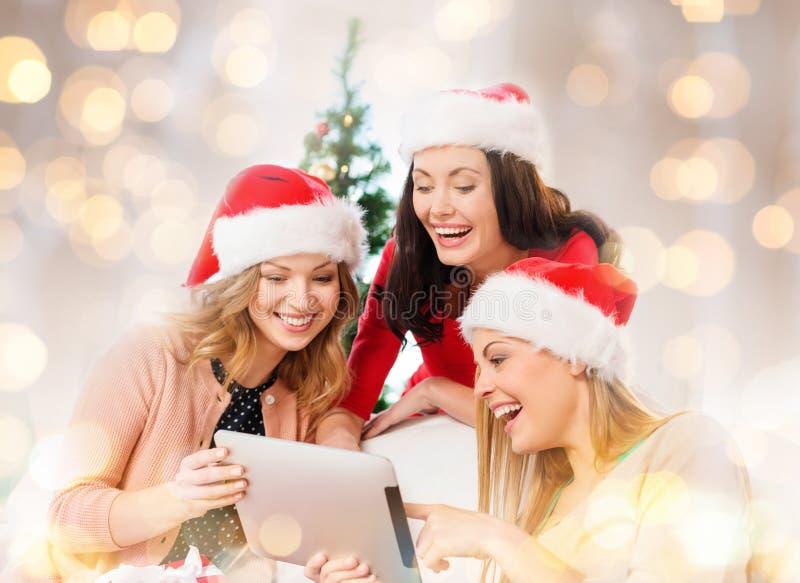Donne felici in cappelli dell'assistente di Santa con il pc della compressa immagine stock libera da diritti