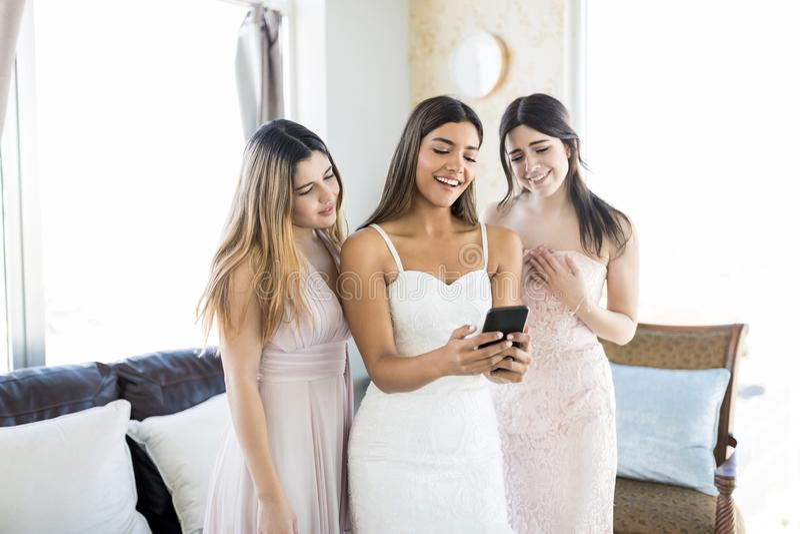 Donne felici che guardano le immagini sul telefono cellulare alla sede di nozze immagini stock
