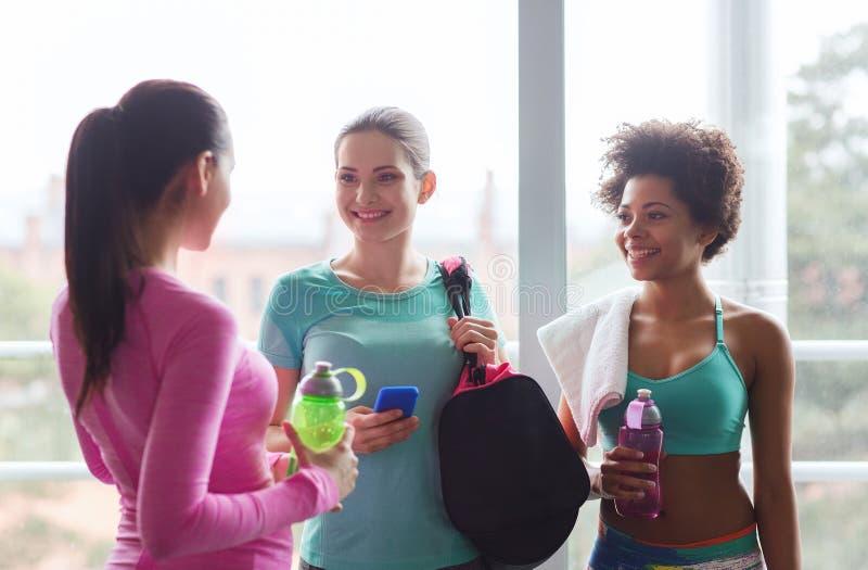 Donne felici con le bottiglie di acqua in palestra immagini stock libere da diritti