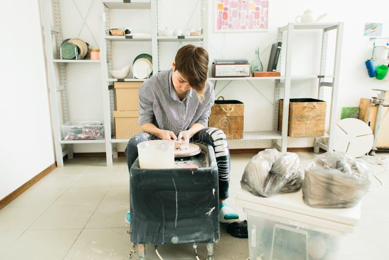 Donne graziose che lavorano al tornio da vasaio dentro lo studio immagini stock libere da diritti