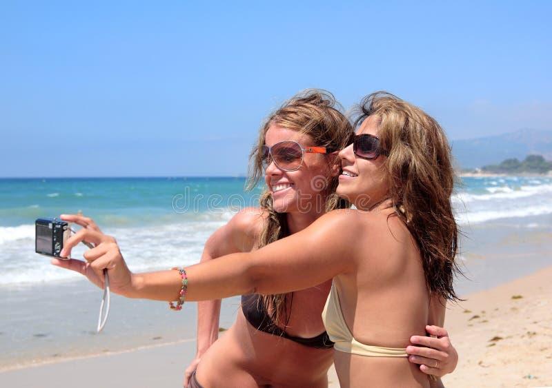 Donne graziose sulla spiaggia piena di sole immagine stock