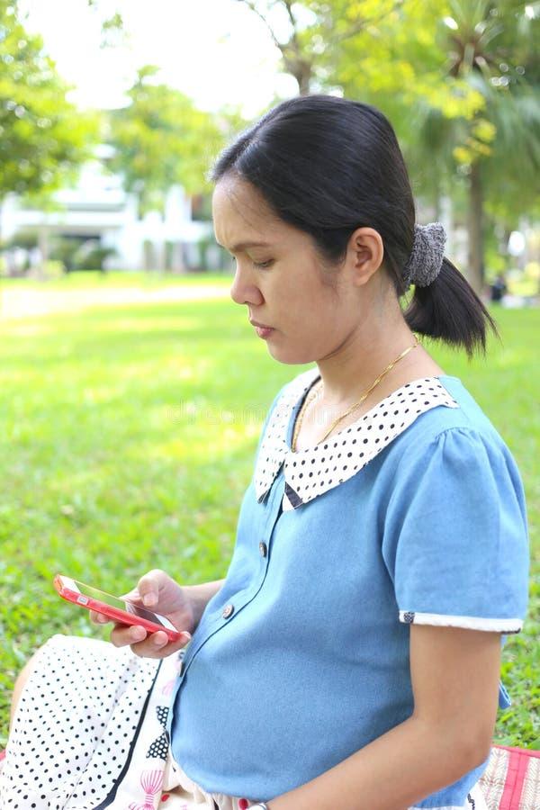 Donne incinte che per mezzo degli smartphones per cercare informazioni su immagini stock