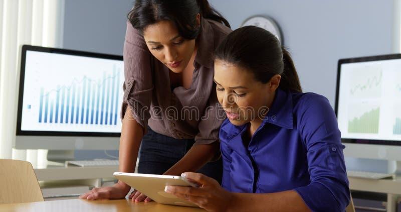 Donne ispane di affari che lavorano con il collega sul computer della compressa immagini stock