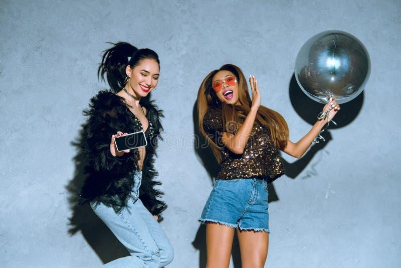 donne multietniche alla moda con lo smartphone ed il pallone divertendosi insieme immagini stock libere da diritti