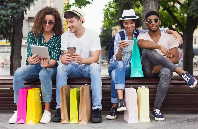 Donne multirazziali che per mezzo degli aggeggi mentre sedendosi sul banco fotografie stock