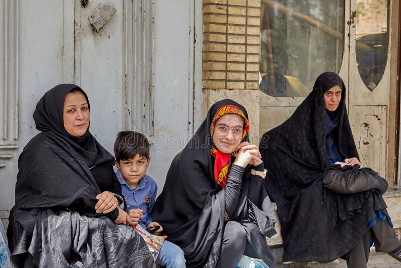 Donne musulmane con il bambino che si siede alla fermata dell'autobus, Kashan, Iran immagini stock libere da diritti