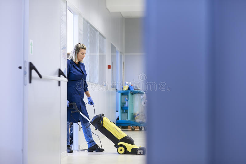 Donne nel luogo di lavoro, pavimento di lavaggio del pulitore femminile professionale dentro fotografia stock libera da diritti
