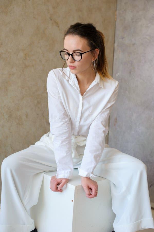 Donne nel sedile bianco dei vestiti di modo sul cubo fotografia stock
