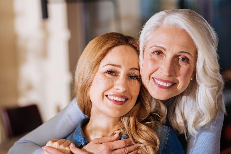 Donne piacevoli emozionali che sorridono e che abbracciano mentre incontrandosi fotografie stock
