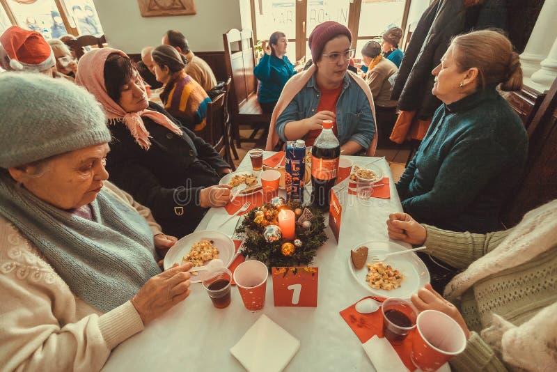 Donne povere anziane pranzando alla cena di carità di Natale per il senzatetto fotografie stock libere da diritti