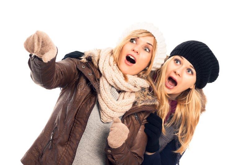 Donne scosse nell'indicare dei vestiti di inverno fotografia stock