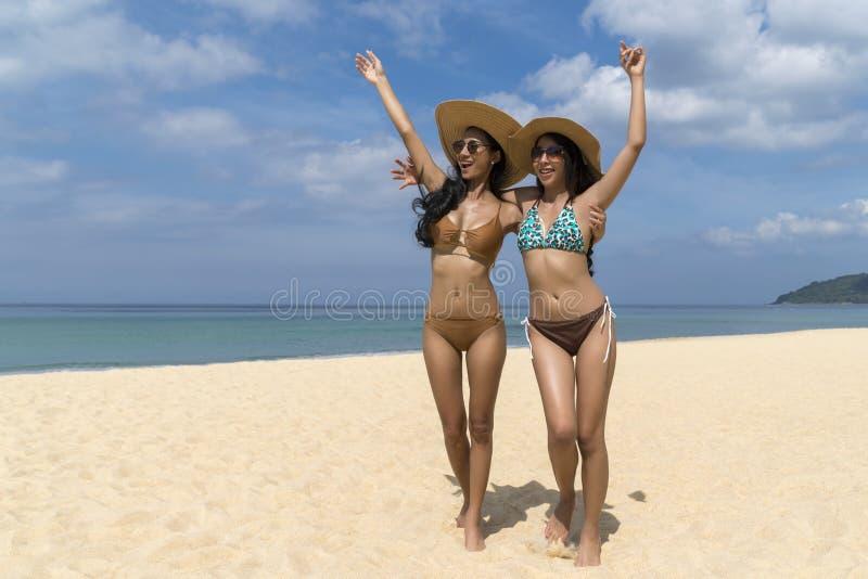 Donne sexy asiatiche in bikini, nel cappello di paglia d'uso sorridente e nei sunglass, camminanti alla spiaggia, viaggio delle v fotografia stock libera da diritti