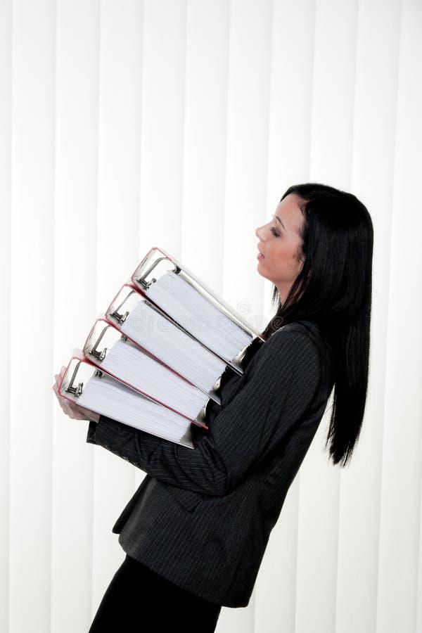 Donne sfavorite con lo sforzo ed archivi nell'ufficio fotografia stock