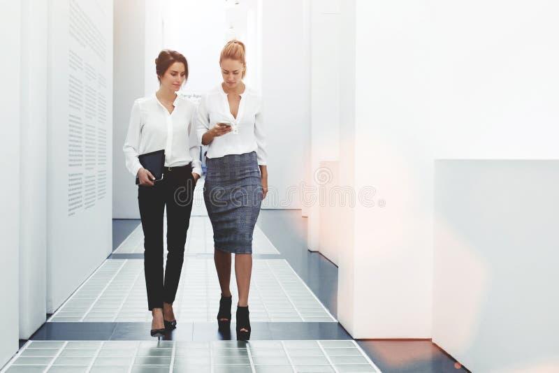Donne sicure che leggono informazioni sulle notizie di finanza mentre camminando nel corridoio della società durante la pausa di  fotografia stock libera da diritti