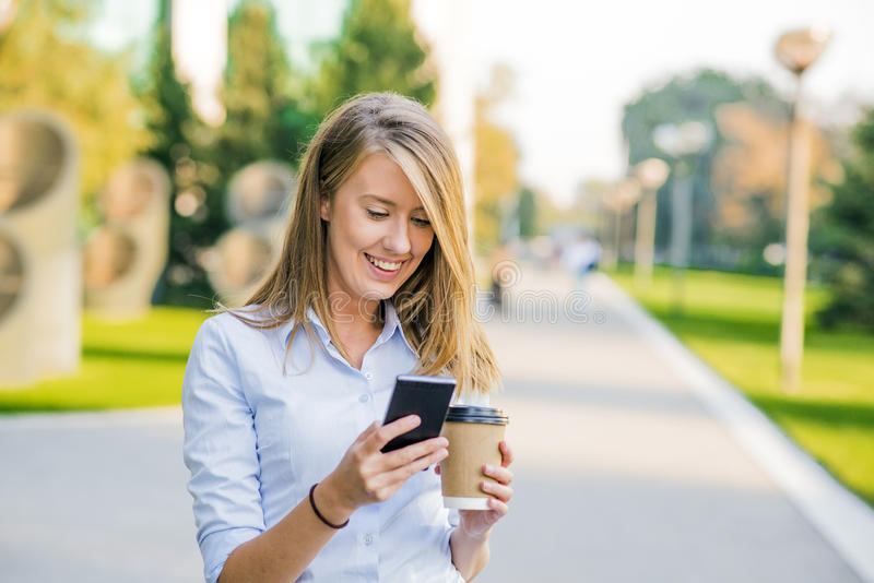 Donne sicure che leggono informazioni sulle notizie di finanza mentre camminando nel corridoio della società durante la pausa di  fotografie stock