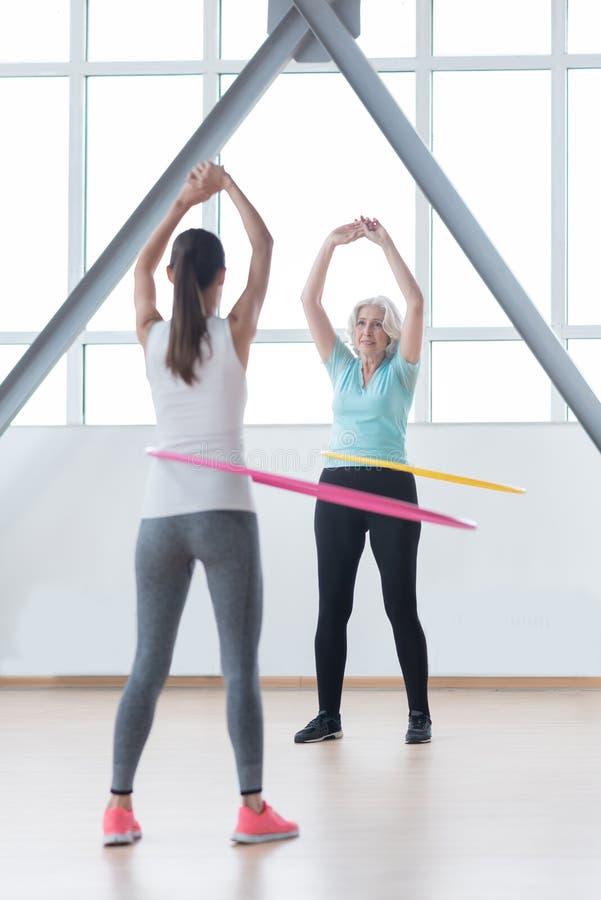 Donne sicure positive che usando i hula-hoop per prepararsi fotografia stock libera da diritti