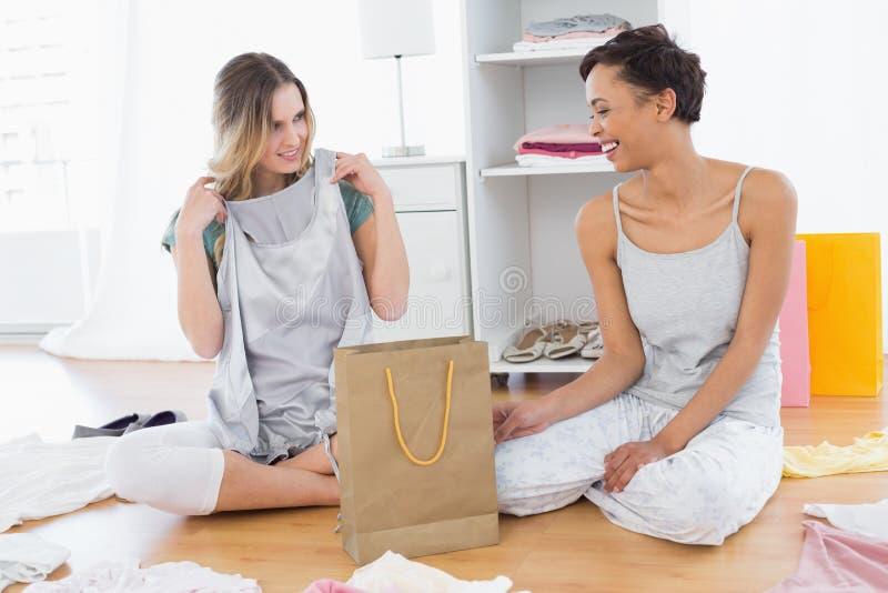 Donne sorridenti che si siedono sul pavimento con il sacchetto della spesa fotografia stock